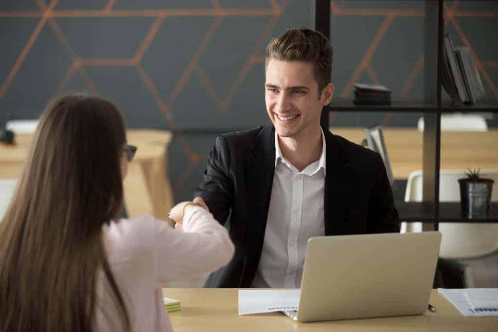 Employer Branding Massnahmen: Lächelnder Arbeitgeber stellt neue Mitarbeiterin ein