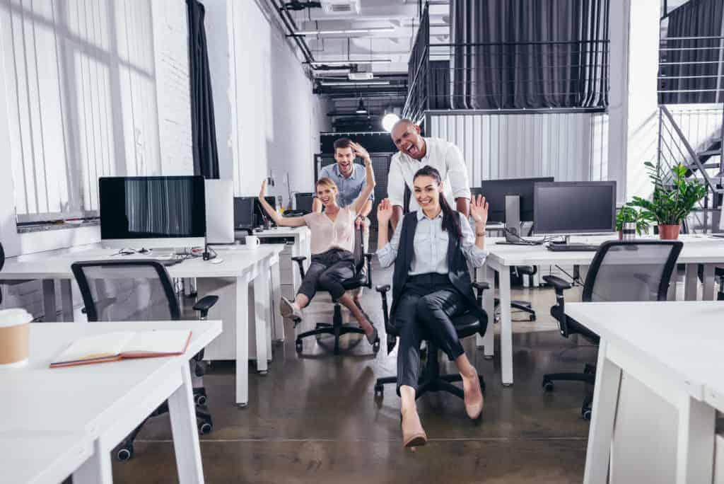 Glückliche Mitarbeiter mit viel Spaß im Job dank gesteigerter Arbeitgeberattraktivität