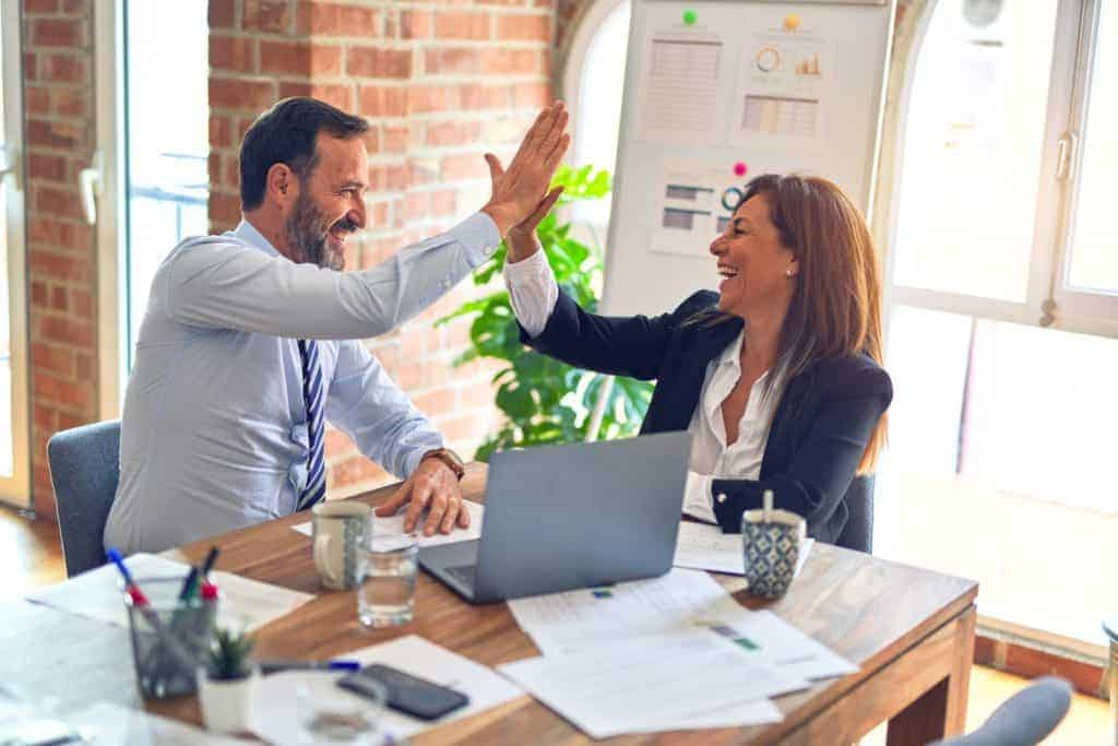 Glückliche Personaler dank starker Arbeitgebermarke geben sich High-Fives