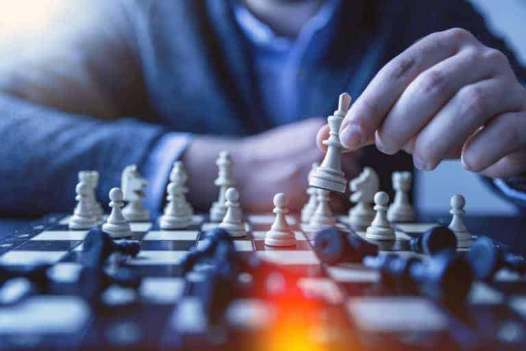 Schachbrett mit Hand eines Spielers als Analogie für Employer Branding Strategien