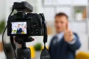 Typische Szene in Imagefilmen, Mann in Anzug und Krawatte zeigt Daumen hoch und lächelt in die Videokamera