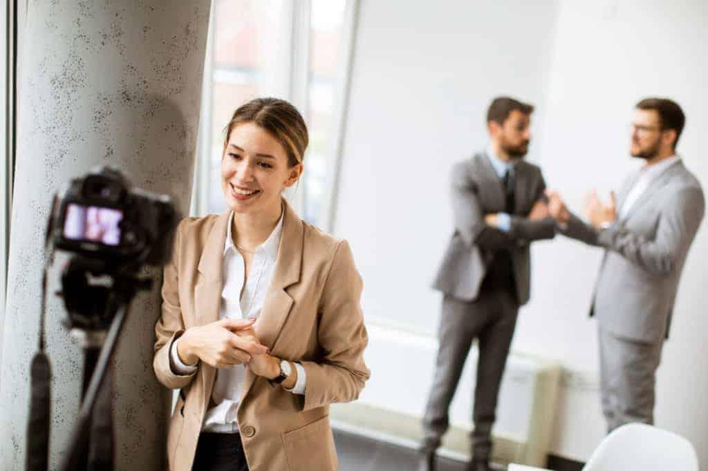 Junge Geschäftsfrau schaut beim Imagefilm-Dreh in die Kamera, während Geschäftsleute im Büro zusammenarbeiten