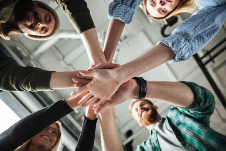 Employer Branding: Kollegen im Büro halten sich an Händen und zeigen starken Zusammenhalt