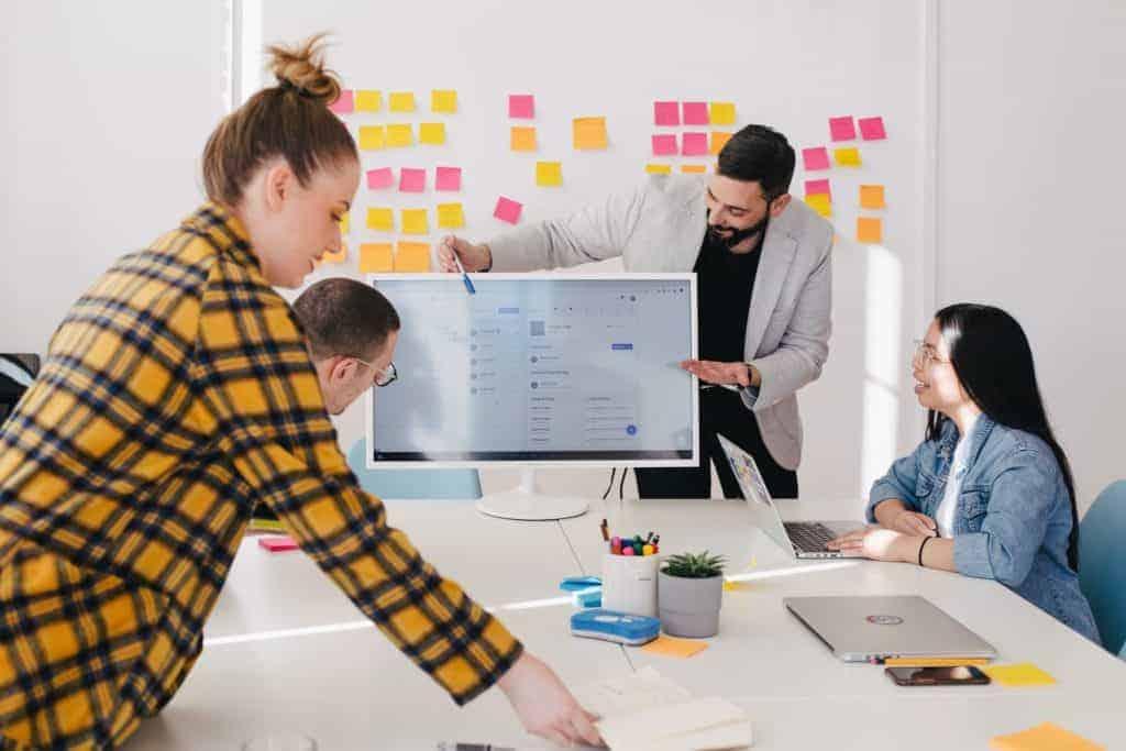 Strategische Planung und Aufstellung von Zielen fürs eigene Employer Brandings während Meeting mit vier Personen